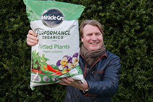 David Domoney - Chartered Horticulturalist - holding up bag of Evergreen Garden Care as he becomes their new brand ambassador